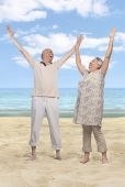 Senior couple doing laughing exercise on the beach