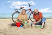 Senior couple making sand castle on the beach