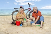 Senior couple making sand castle on the beach and laughing