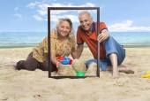 Senior couple showing sand castle through an empty picture frame on the beach