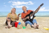 Senior man with his wife playing guitar on the beach