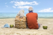 Rear view of a senior couple sitting on the beach