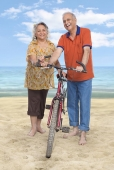 Senior couple with a bicycle on the beach