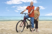 Senior couple riding a bicycle on the beach
