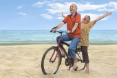 Senior couple riding a bicycle on the beach and cheering