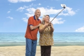 Senior couple taking selfie with a mobile phone on the beach