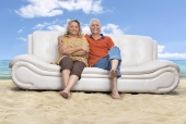 Portrait of a senior couple sitting on a couch on the beach