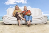 Senior couple sitting on a couch and watching tv on the beach