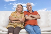 Portrait of a senior couple sitting on a couch and laughing
