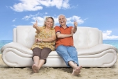 Senior couple sitting on a couch on the beach and showing thumbs up signs